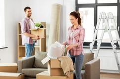 Happy couple with stuff moving to new home stock photo