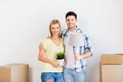 Couple with flower and lamp moving to new home. Home, people, repair and real estate concept - smiling couple with cardboard boxes, lamp and flower moving to new royalty free stock photography