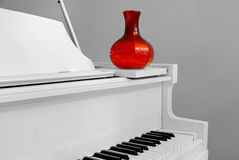Home Piano Detail. Corner of a piano with a red vase in a home interior Stock Image