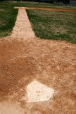 Home plate on baseball field. A baseball base on a little league field in focus royalty free stock photography