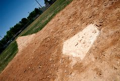 Home plate on baseball field. A baseball base on a little league field in focus stock photography