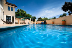 Home with a pool. WS: Tranquil swimming pool adjacent to a substantial home, in an enclosed patio Royalty Free Stock Photography