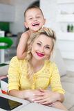 Home portrait of a happy mother with her son. Home portrait of a happy mother and her son,6 years old,sitting together on a large bright kitchen behind a white Royalty Free Stock Image