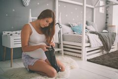 Home portrait of young pregnant woman preparing for childbirth and doing everyday homework at nursery. Home portrait of young pregnant woman preparing for Royalty Free Stock Image