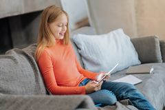 Positive nice girl sitting on the sofa. At home. Positive nice cheerful girl sitting on the sofa and holding a tablet while resting at home Royalty Free Stock Photo