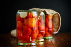 Home preservation. Canned in a glass jar ripe tomatoes. Home preservation. Canned in a glass jar ripe tomatoes on a wooden table royalty free stock photography