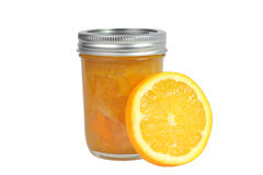 Home Preserves Orange Marmalade. Home canning - a jar of home preserved orange marmalade jam displayed with an orange slice isolated on white Stock Photos