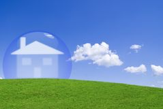 Home protection. House protected by a glass bubble in a green meadow Stock Image