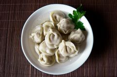 Home / purchased dumplings in a broth with greens.Dumplings are. Home / purchased dumplings in a broth with greens.nDumplings are laid out in a deep white bowl Stock Photos