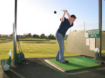 Home on the Range. A junior golf champion practices on the golf range Stock Image