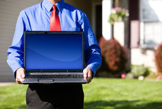 Home: Real Estate Agent Holds Laptop with Blank Screen royalty free stock photo