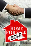 Home real estate sale. Two business men shaking hands over money transaction deal Royalty Free Stock Photography