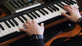 Home recording music studio. Hands playing on piano with mixing and mastering board and soundboard. Sound engineer composer writin. G pop rock song on piano at stock video footage