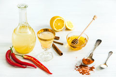 Home red pepper tincture in a glass and fresh lemons on the white wooden background Stock Photography