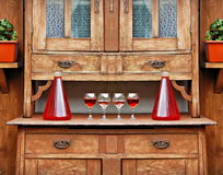 Home red wine in a glasses and bottles on the top of the vintage wooden cupboard. Home red wine in a four glasses and two bottles on the table top of the Royalty Free Stock Images