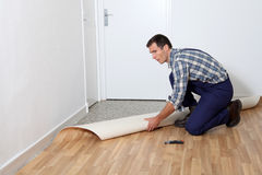 Home reforming. Closeup of artisan installing ground floor in room Royalty Free Stock Photo