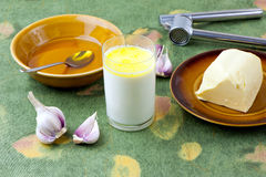 Home remedy. Home made remedy for flu: glass of hot milk with honey, butter and garlic Stock Photo