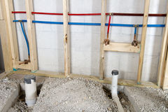 Hot and Cold Running Water Plumbing Pipes. Home remodeling project where pipes and lines for hot and cold running water are being installed. Red and blue lines royalty free stock photo