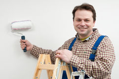 Home renovate. Man on ladder paiting wall by roller Stock Images