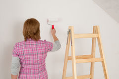 Home renovate. Woman painting wall by roller Stock Photo