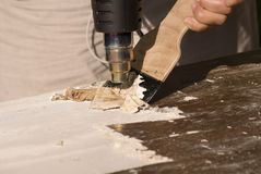 Home Renovation. Portrait of renovation; removing old paint using scraper and heat gun Royalty Free Stock Photo