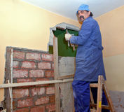 Home renovation. It's time for home renovation and redecoration. Worker is filling holes in the wall with bricks and cement that will allow owner of this flat to Royalty Free Stock Photography