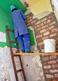 Home renovation. It's time for home renovation and redecoration. Worker is filling holes in the wall with bricks and cement that will allow owner of this flat to Stock Images