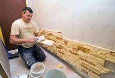 Home renovation. A worker putting new decorative tiles on the walls Stock Photos