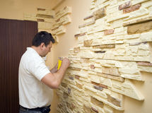 Home renovation. A worker putting new decorative tiles on the walls Royalty Free Stock Photos