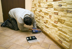 Home renovation. A worker drilling under new decorative tiles on the walls Royalty Free Stock Images