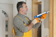 Home renovation, caulking door with silicone Stock Image