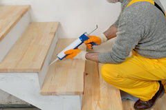 Home renovation, caulking wooden stairs with silicone. Construction worker caulking wooden stairs with silicone glue using cartridge, home renovation Stock Image