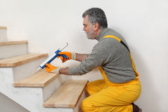 Home renovation, caulking wooden stairs with silicone Stock Photography