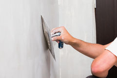 Home Renovation. Construction worker holding plastering trowel, smoothing wall defects Stock Photos