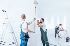 Home renovation crew finishing interior. Home renovation crew in overalls finishing white interior using different equipment royalty free stock photo