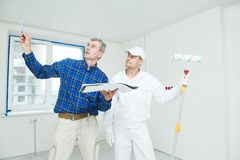 Foreman designer and painter worker discussing painting project tas stock photo