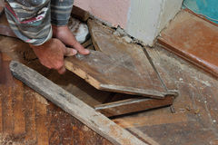 Home renovation. Hand of worker removing old oak parquet Stock Photo