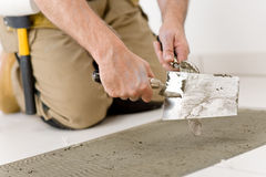 Home renovation - handyman laying tile. Home improvement, renovation - handyman laying tile, trowel with mortar royalty free stock photos