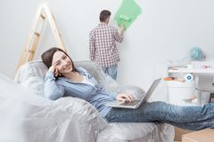 Home renovation. Happy couple doing home renovations, the men is painting the room and the women is relaxing on the armchair and connecting with a laptop royalty free stock photo