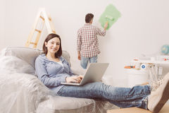 Home renovation. Happy couple doing home renovations, the men is painting the room and the women is relaxing on the armchair and connecting with a laptop stock photography