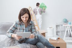 Home renovation. Happy women relaxing and connecting with her tablet while a painter is painting the room, home renovation concept royalty free stock image