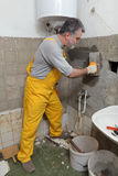 Home renovation, mason fixing wall. Worker spreading mortar with trowel to wall in a bathroom Stock Photos
