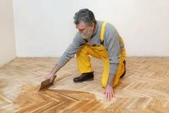 Home renovation, oak parquet varnishing finish Stock Photo