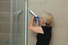 Home renovation, shower cabin fixing with silicone. Woman using silicone cartridge for fixing aluminum batten of shower cabin royalty free stock photos