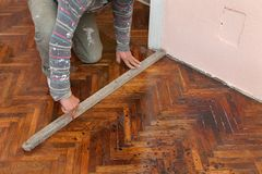 Home renovation. Worker  marking parquet floor with pencil before cutting Royalty Free Stock Photos