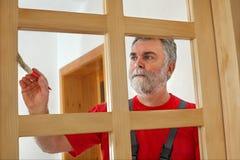 Home renovation, worker painting wooden door, varnishing Stock Image