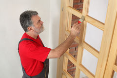 Home renovation, worker painting wooden door, varnishing Royalty Free Stock Photos