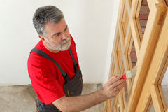 Home renovation, worker painting wooden door, varnishing Royalty Free Stock Photo