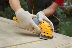 Home renovation, worker sanding wooden door Royalty Free Stock Photography