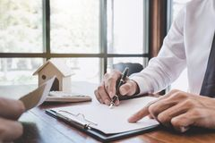 Home for rent concept, broker agent presenting and consult detail to customer to making the decision a home estate loan to. Customer sign form agreement, home stock images